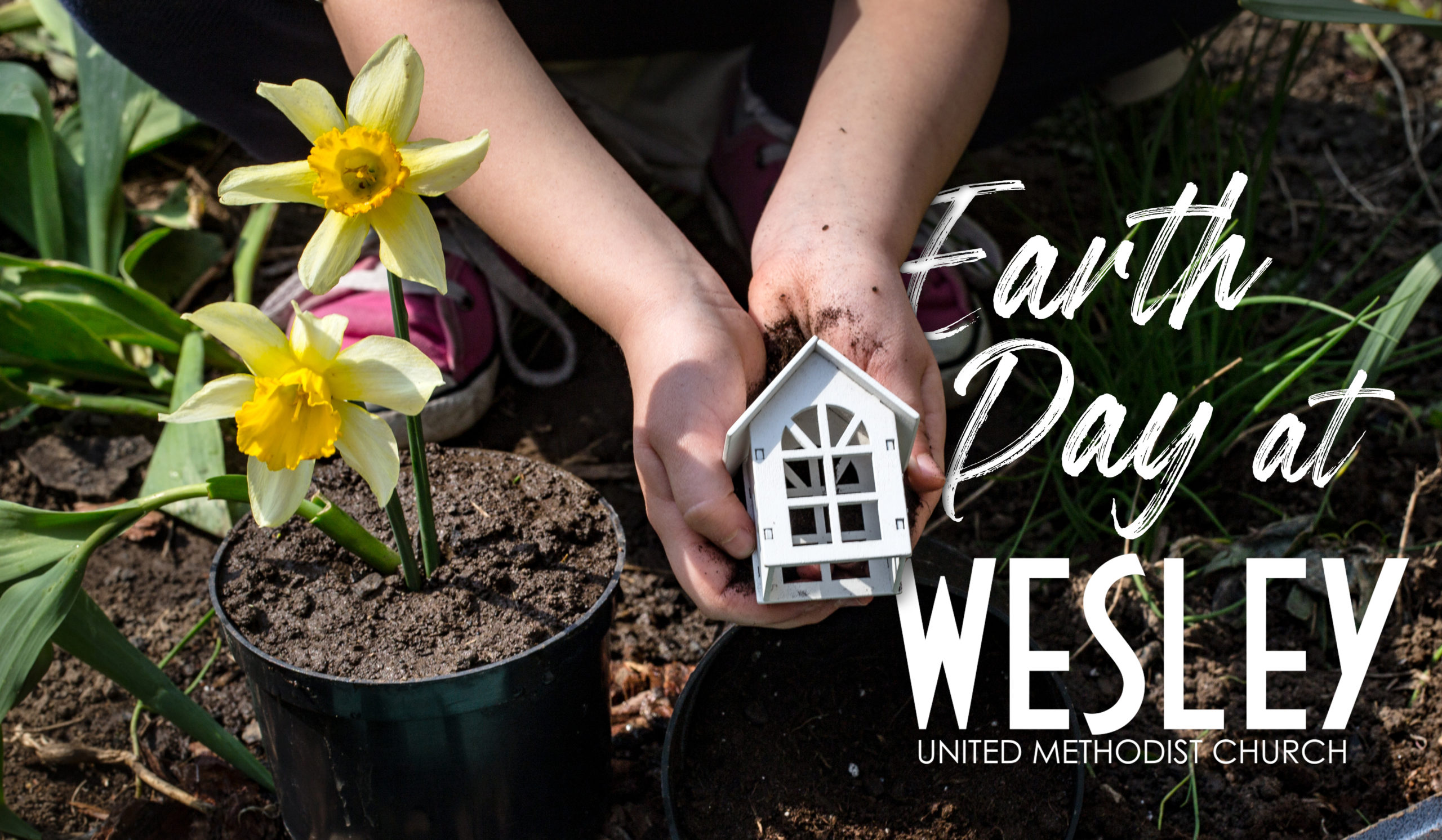 Earth Day .A child in the background of the garden holding a small wooden house. Wooden letters with the inscription home